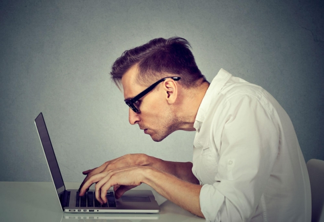 Worker hunched over laptop